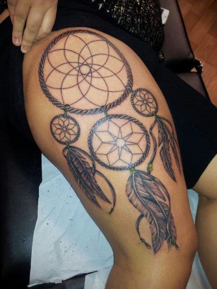 large dreamcatcher, with green beads, thigh tattoos for girls, black shorts, black leather bed