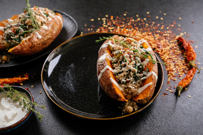dinner ideas for two, stuffed sweet potatoes, with sauce and thyme for garnish, in black plates, on black table