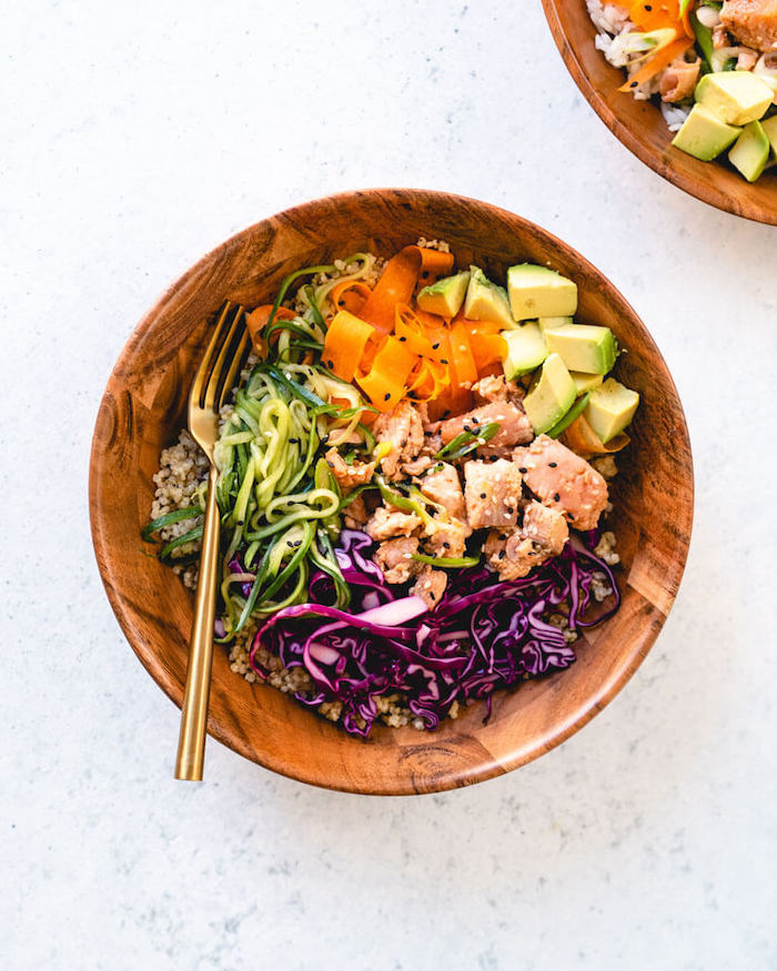 seared salmon, zucchini and carrots noodles, quinoa and avocado, in a wooden bowl, dinner ideas for tonight, white table