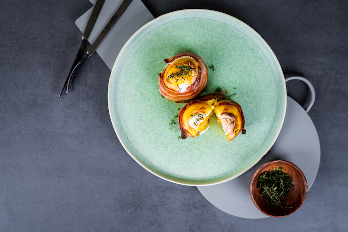 egg filled halved potatoes, wrapped with bacon slices, baked potato volcanoes, arranged on blue plate
