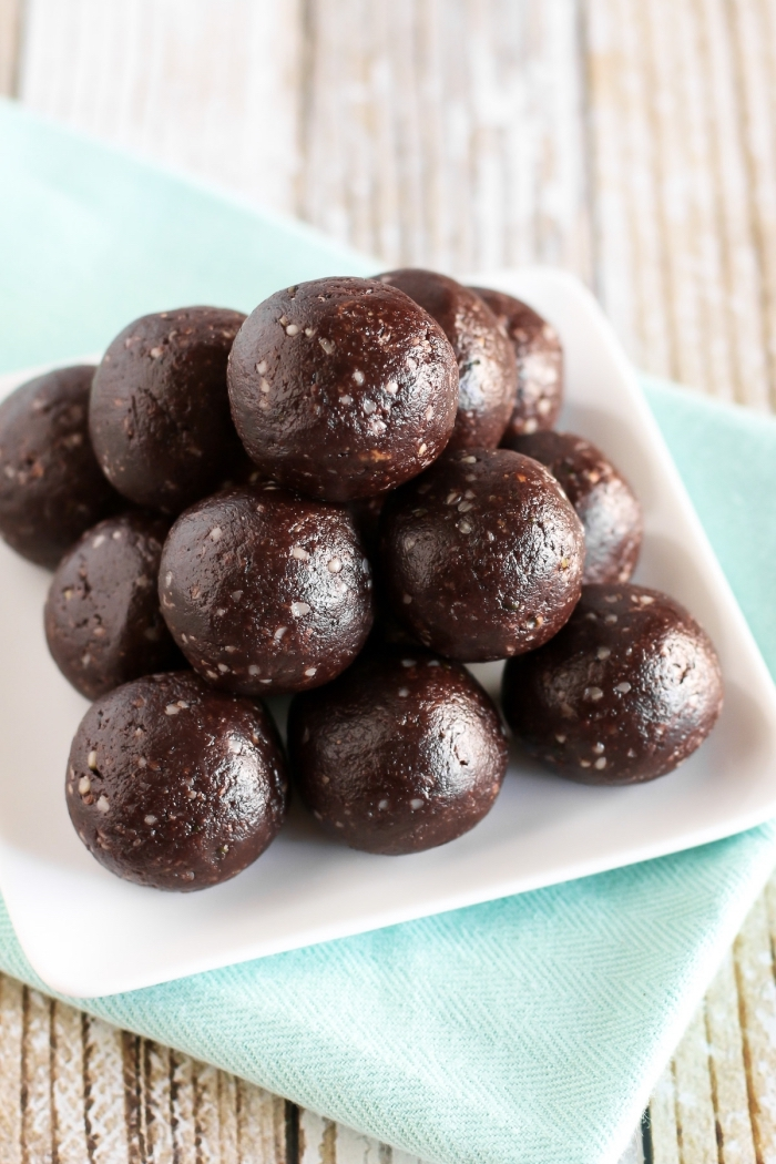 chocolate truffles, arranged in a pyramid, in a white plate, blue cloth, wooden table, no bake energy balls
