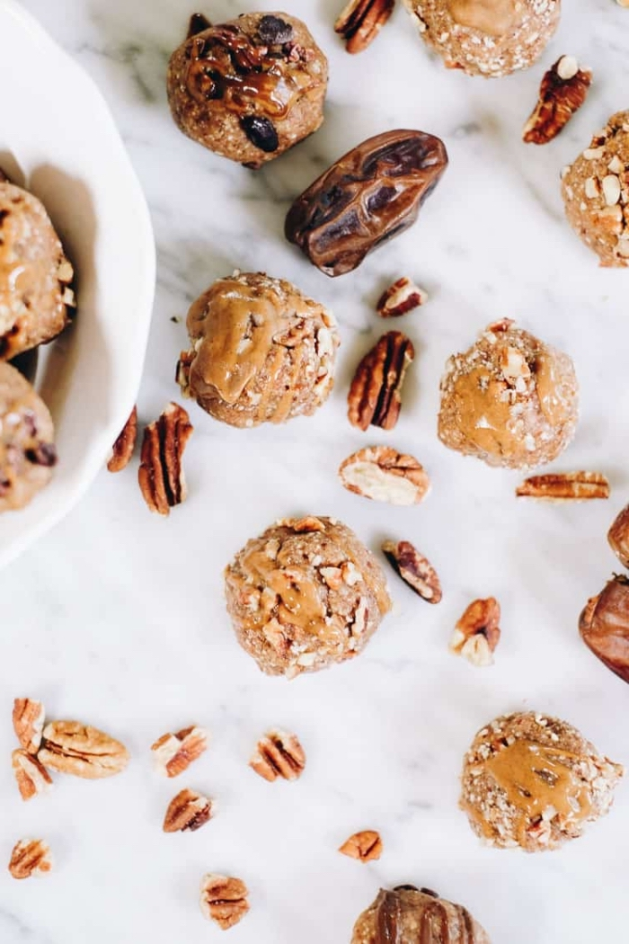 dates and walnuts, scattered around the table, energy bites, with peanut butter drizzle on top