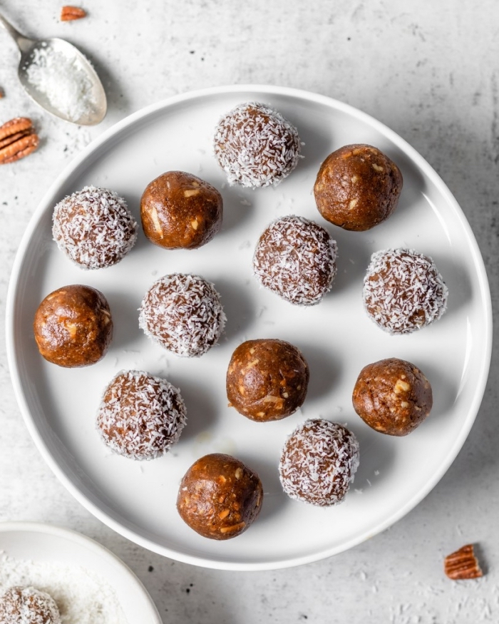 walnuts scattered on the table, no bake energy balls, covered with coconut flakes, white plate