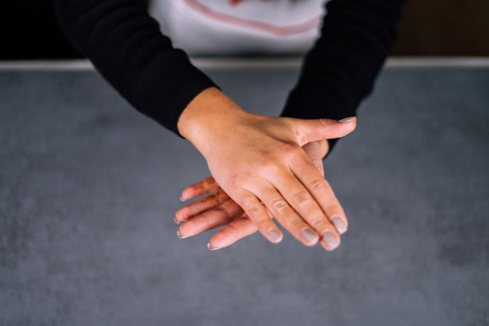 female hands, with grey nail polish, shaping chocolate mixture, energy balls, granite countertop