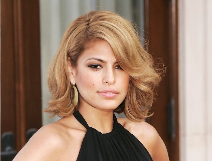 eva mendes, wearing black dress, large earrings, caramel brown wavy hair, shoulder length layered hair