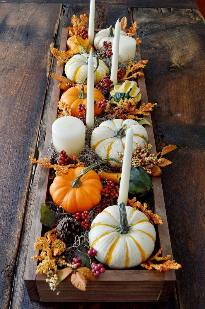 small pumpkins, pine cones, fall leaves, candles inside wooden crate, on wooden table, autumn decor