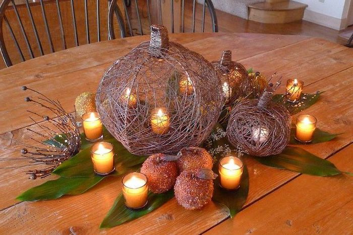 faux pumpkins, candles inside, candy apples, autumn decor, candles in glasses, wooden table