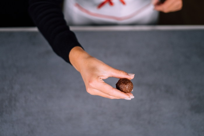 granite countertop, peanut butter protein balls, female hands, with grey nail polish, shaping chocolate into a ball