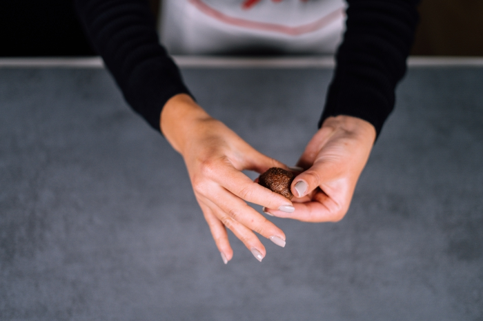 peanut butter protein balls, female hands, with grey nail polish, shaping chocolate mixture, into a ball