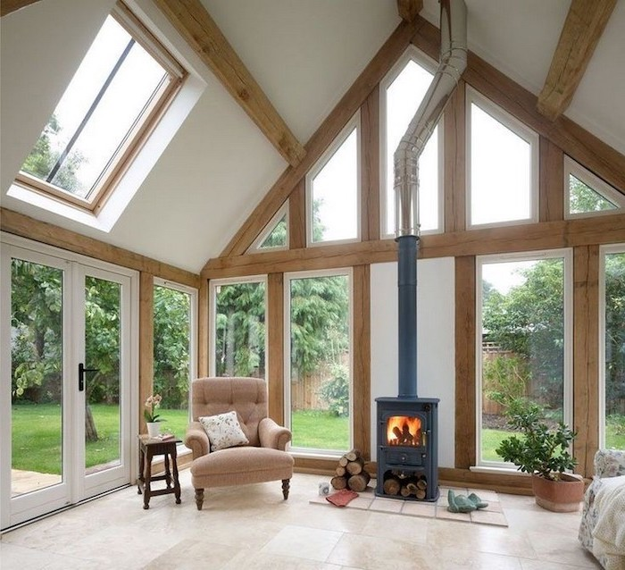 tall windows, tiled floor, beige armchair, vaulted ceiling ideas, ceiling with skylights, wooden beams