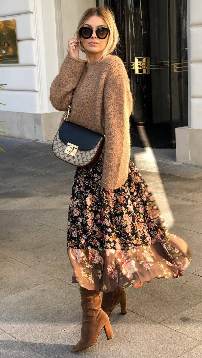 woman wearing sunglasses, brown sweater and floral skirt, brown velvet boots, medium length layered hair, crossbody bag