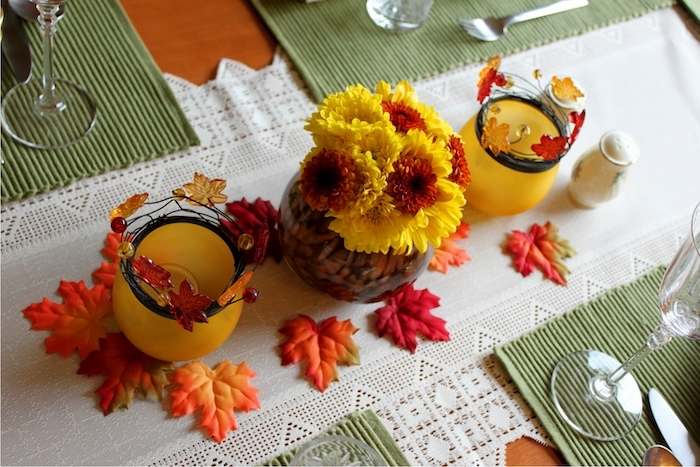 outdoor thanksgiving decorations, yellow and orange, flower bouquet, fall leaves, wine glasses white table runner
