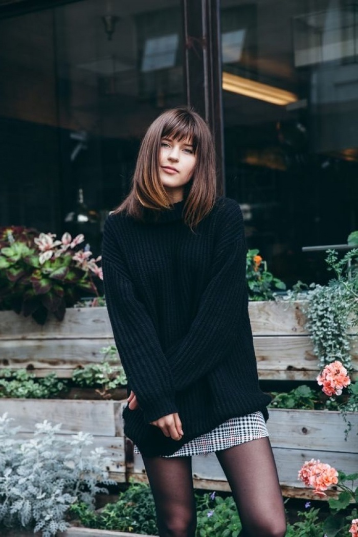 woman wearing black oversized sweater, medium length layered hair, brown hair with bangs, flowers in the background