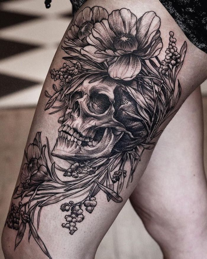 human skull, surrounded by flowers, thigh tattoos for girls, black shorts, tiled floor