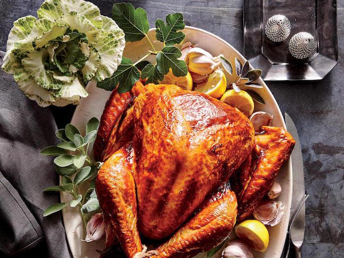 oven roasted turkey, lemon slices, fresh herbs, on the side, garlic cloves, white plate, black table, black cloth
