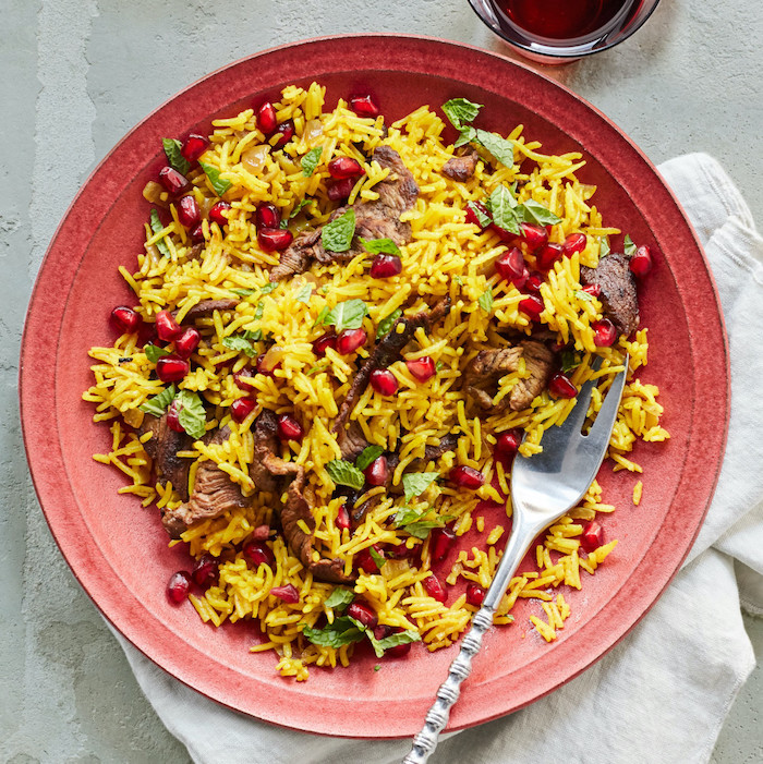 fried rice with steak, what's for dinner tonight, pomegranate seeds for garnish, in red plate, on white table