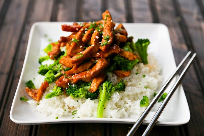 pork with sesame seeds, with broccoli and rice, in white plate, metal chopsticks on the side, what should i make for dinner, wooden table