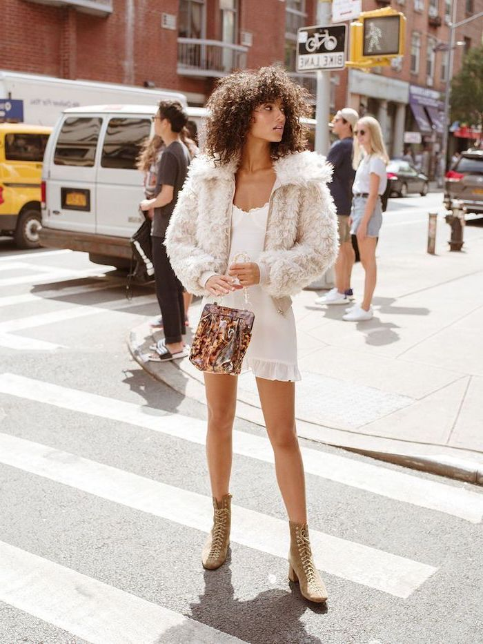 medium length layered hair, woman in the middle of the street, wearing white dress and jacket, brown curly hair