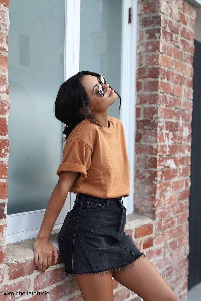 woman leaning on brick wall, wearing black denim skirt, orange t shirt and sunglasses, shoulder length hair, black hair in a bun