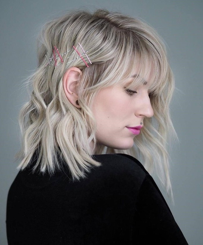 woman with wavy blonde hair with bangs, wearing black blouse, shoulder length hair, pink lipstick