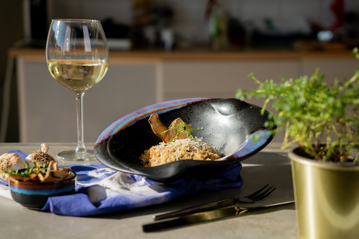 mushroom risotto recipe, risotto placed in black bowl, glass of white wine on the side, topped with fresh thyme and parmesan