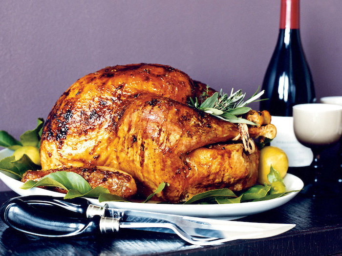 wine bottle, black wooden table, oven roasted turkey, lemon slices, fresh herbs, on the side, purple wall