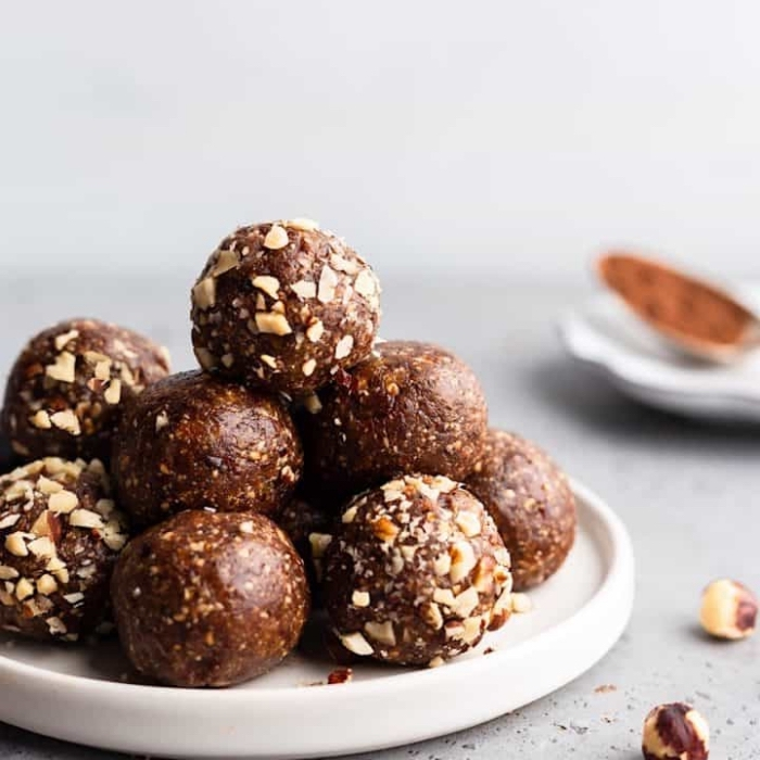 chocolate truffles, with nuts, on white plate, power balls recipe, blurred background