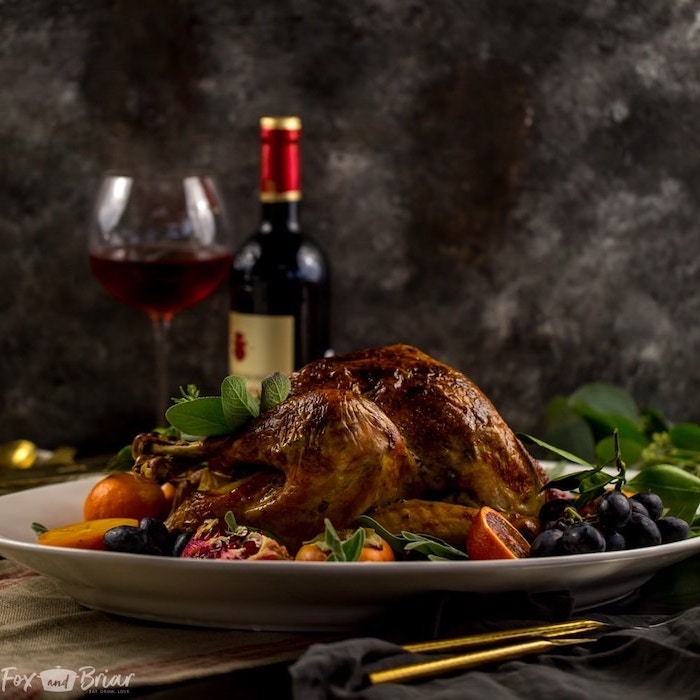 wine glass, wine bottle, oven roasted turkey, grapes and pomegranates, fresh herbs, on the side, white plate