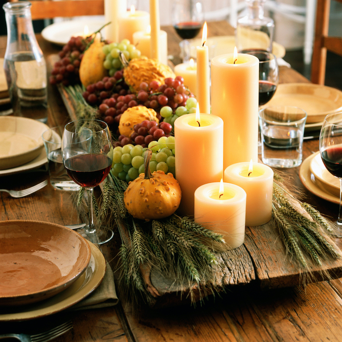 grapes and pumpkins, candles and wheat, on wooden log, outdoor thanksgiving decorations, wooden table, plate setting