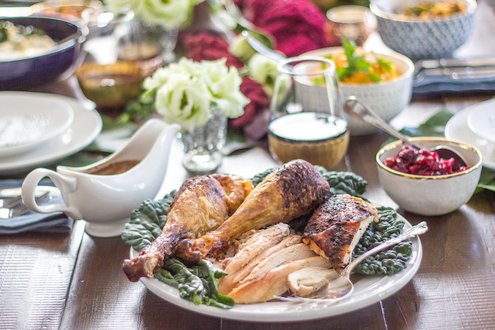carved turkey, white plates, gravy in a jug, cranberry sauce, roast turkey recipe, wooden table, flower bouquets