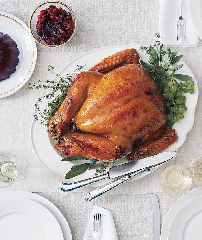 cranberry sauce, white table cloth, roast turkey recipe, fresh herbs, on the side, white plate, wine glasses