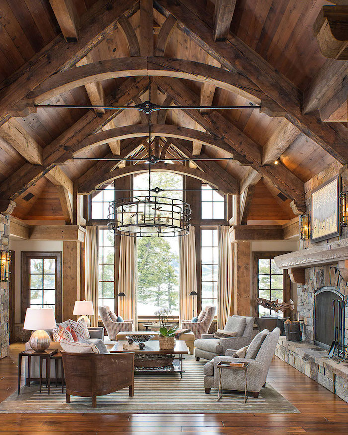 grey armchairs, rustic decor, wooden walls and ceiling, large stone fireplace, cathedral ceiling, tall windows