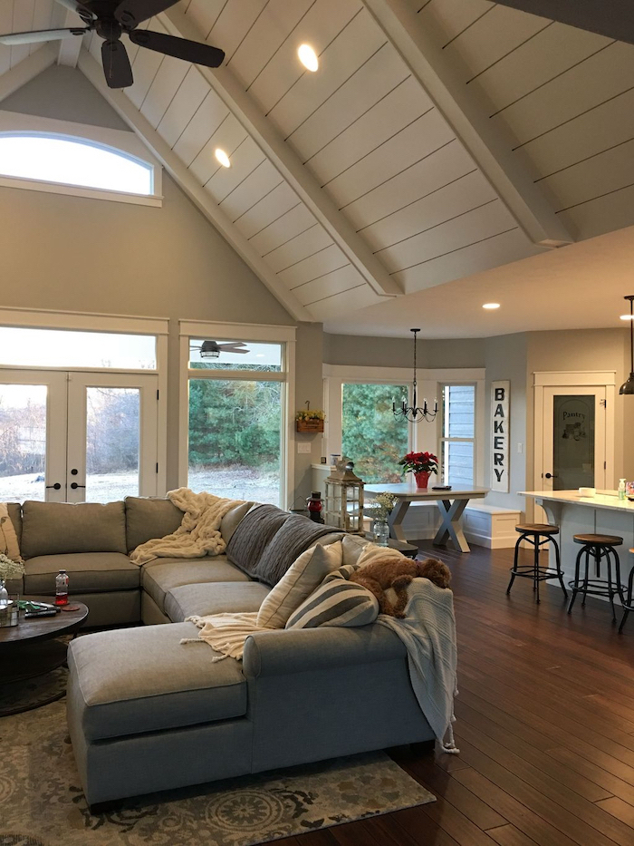 grey corner sofa, wooden floor, vaulted ceiling ideas, printed carpet, throw pillows and blankets