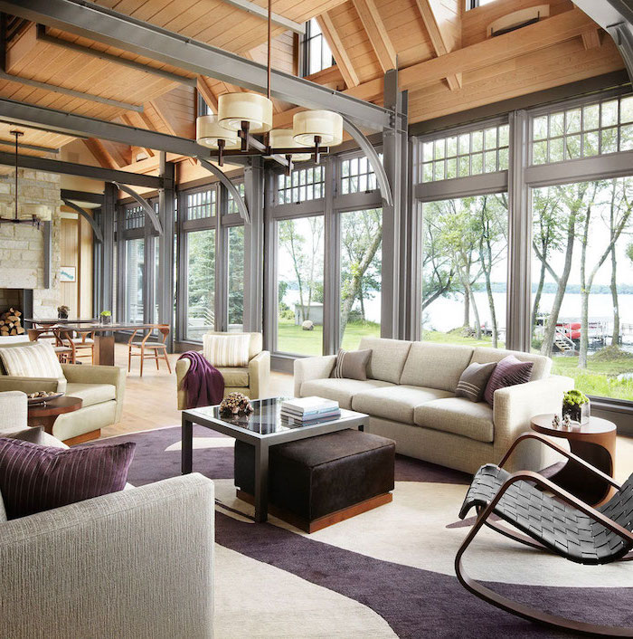 metal beams, vault definition, grey sofas, white and purple carpet, tall windows, stone fireplace wall