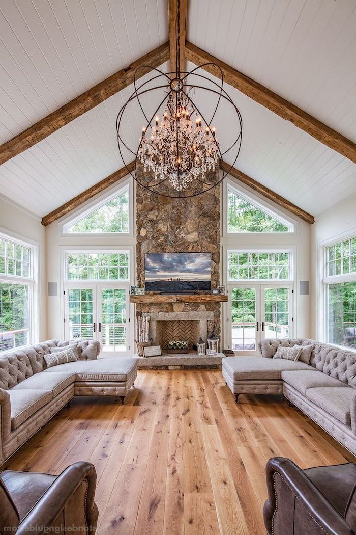 stone fireplace wall, grey corner sofas, brown leather armchairs, wooden floor, vaulted ceiling with beams