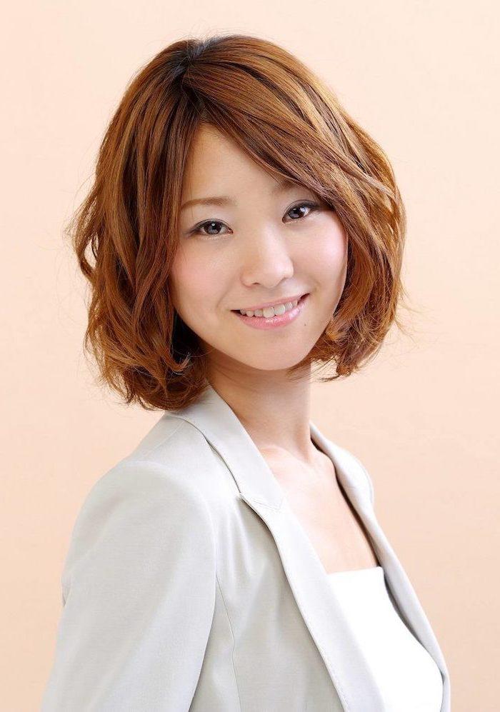 woman smiling, brown wavy hair with side swept bangs, medium length layered hair, wearing grey blazer, white top