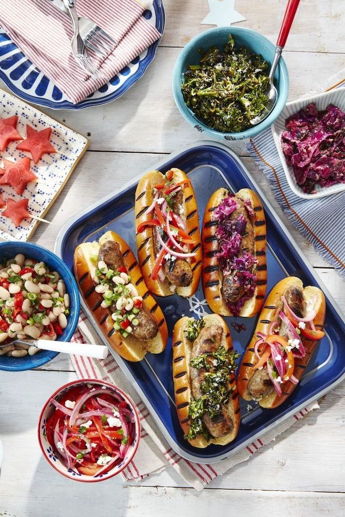 grilled hot dogs, arranged on blue sheet pan, what's for dinner tonight, bowls with different ingredients, white wooden table