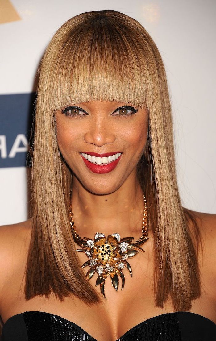 tyra banks smiling, hairstyles for women, caramel brown straight hair with bangs, large necklace