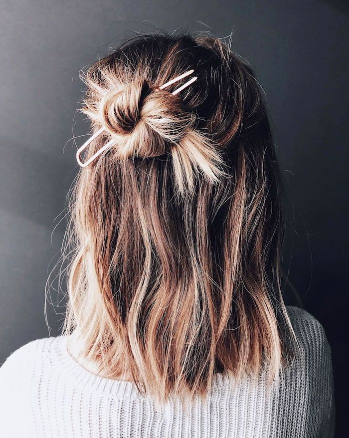 shoulder length bob, woman with balayage blonde hair, half up in messy bun, wearing white sweater