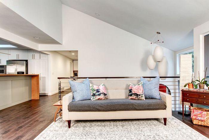 vaulted ceiling lighting, white sofa, floral throw pillows, white walls, metal railing, wooden floor, white carpet