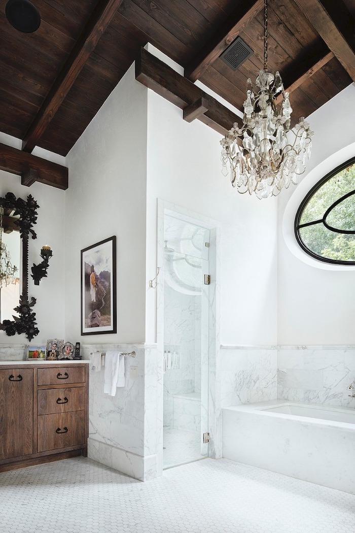 half white, half marble walls, hanging chandelier, wooden ceiling, wooden cupboards, vaulted ceiling