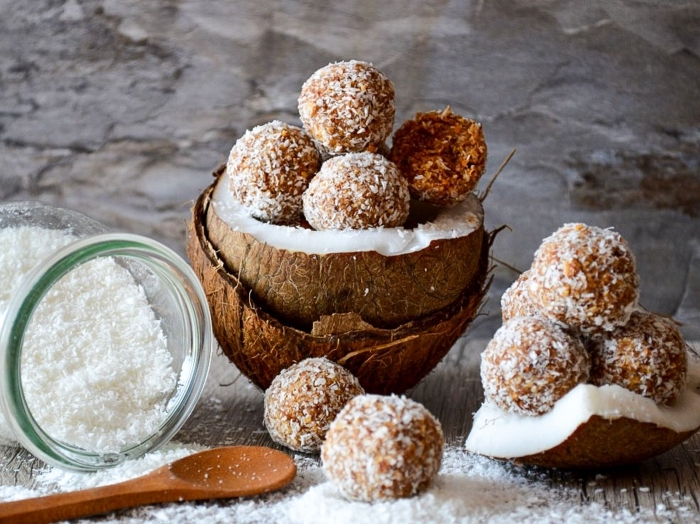 halved coconuts, power balls recipe, coconut flakes, in a glass jar, wooden spoon, peanut butter bites
