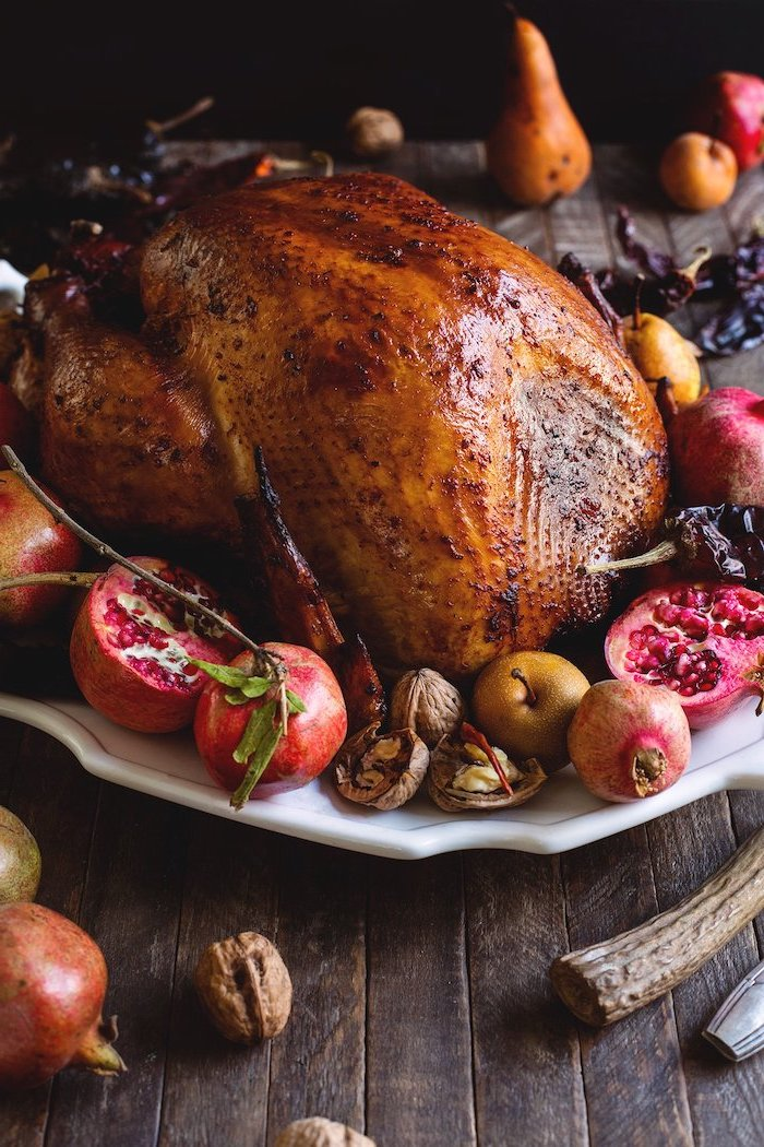 pears and pomegranates, walnuts and apples, on the side, roast turkey recipe, wooden table, white plate