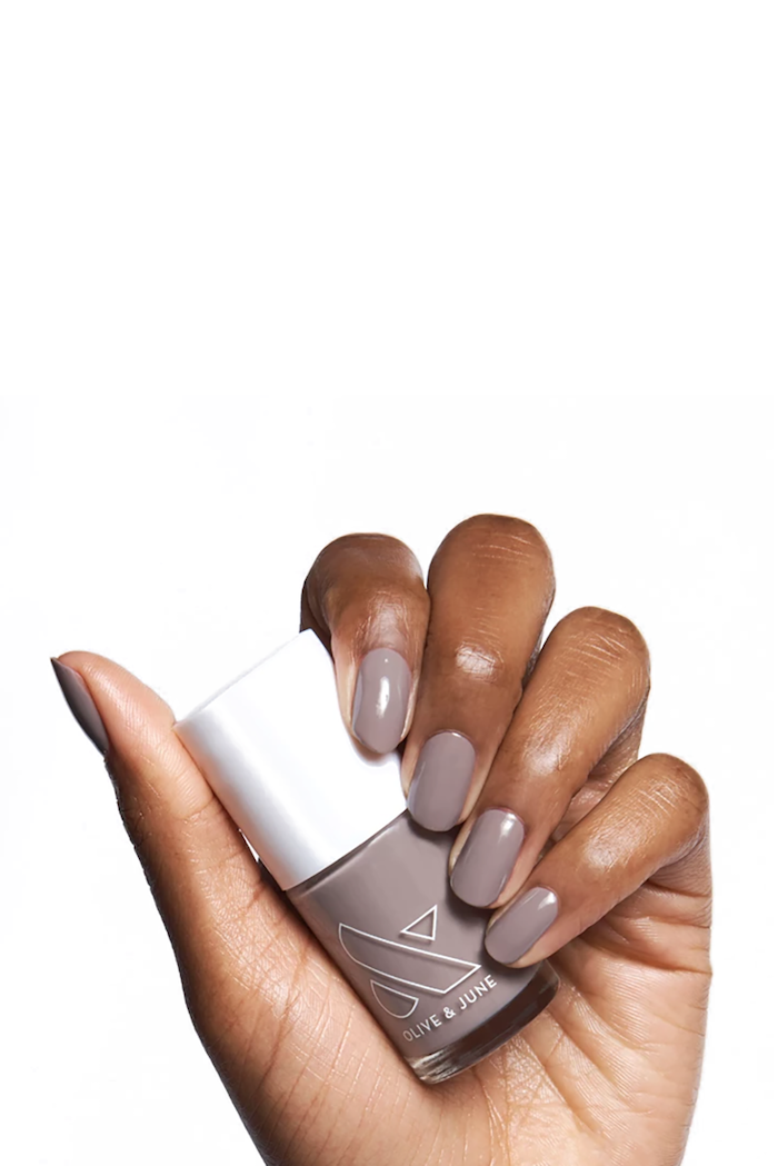 female hand, holding a grey, nail polish bottle, white background, squoval nails, cute nail colors