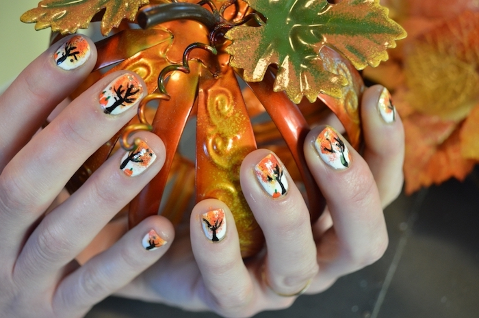 hands holding a ceramic pumpkin, white nail polish, fall nail ideas, trees with fall leaves, nail decorations