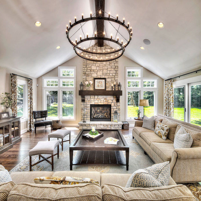 hanging chandelier, beige sofas, throw pillows, vaulted ceiling with beams, wooden table, grey ottomans