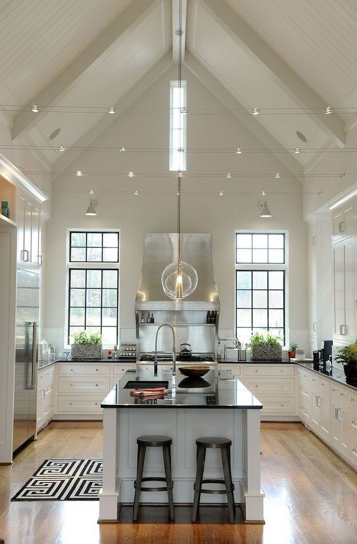 strings of lights, kitchen island, white cupboards, black countertops, vaulted ceiling with beams, wooden floor