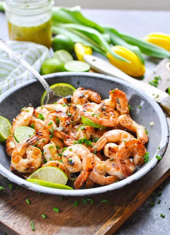 shrimp with lime slices, weight loss meal plan, ceramic bowl, wooden cutting board, silver spoon, chives on top