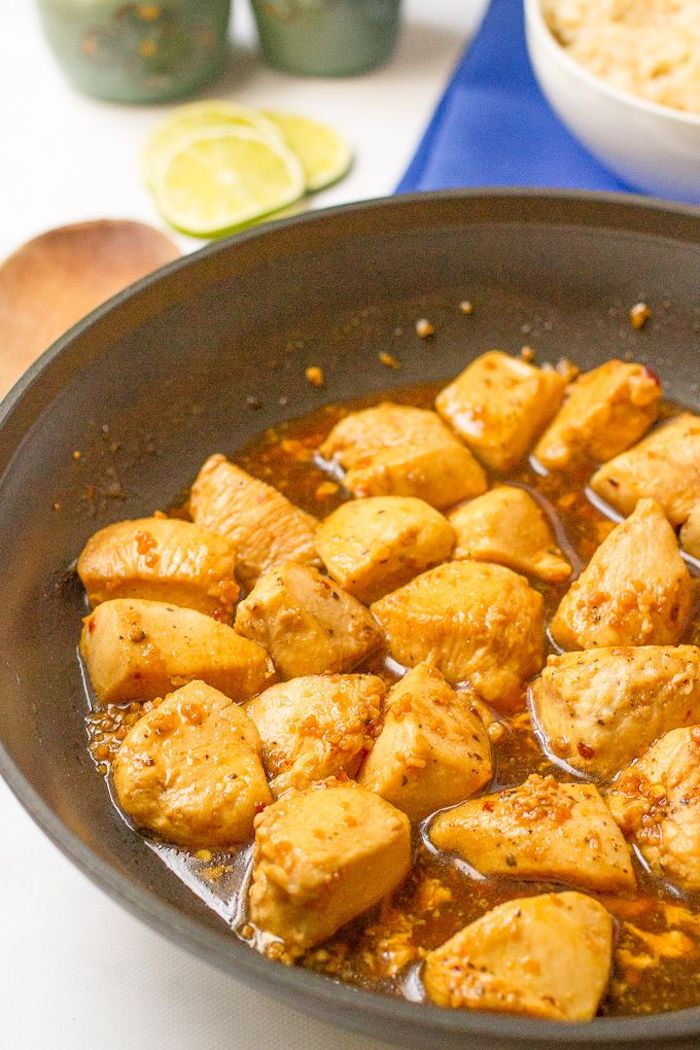 honey garlic chicken, cut into pieces, cooked in skillet, dinner ideas for tonight, lime slices, blue cloth, in the background
