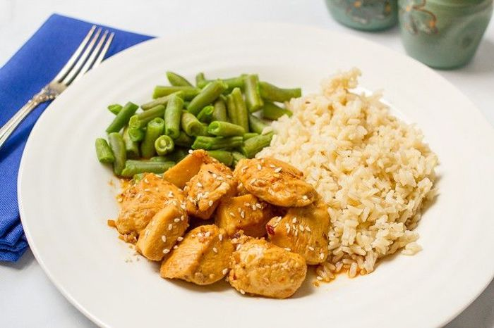 rice and beans, honey garlic chicken, in white plate, dinner ideas for tonight, blue napkin, fork on top, white table